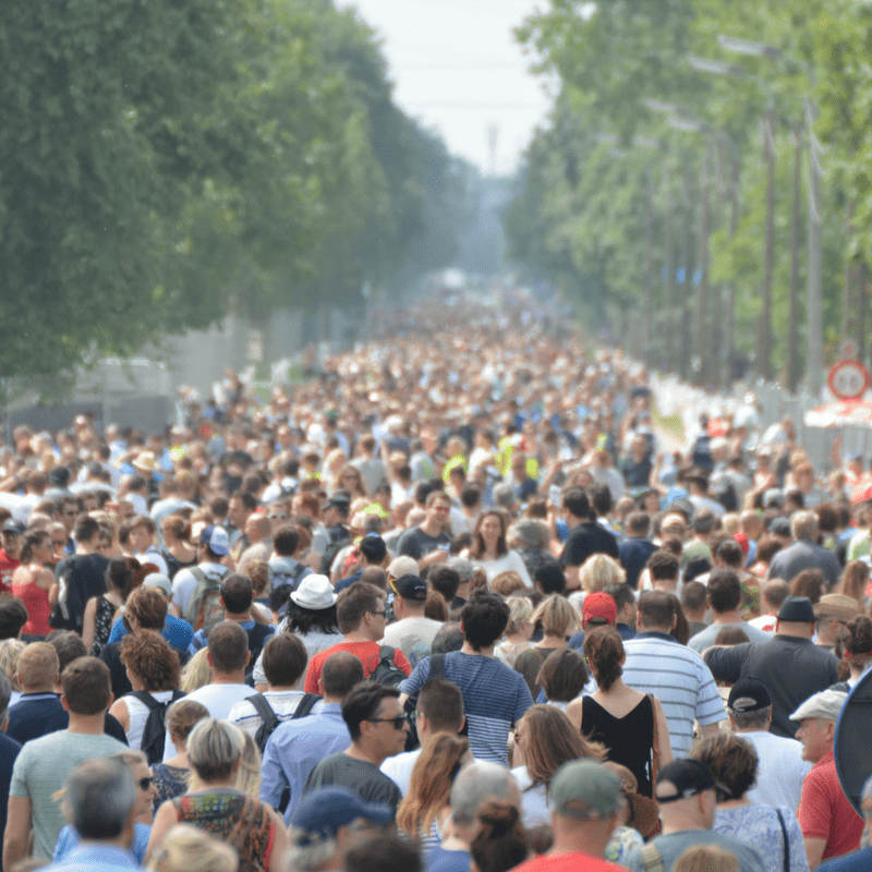 Crowded people in street surrounded by trees